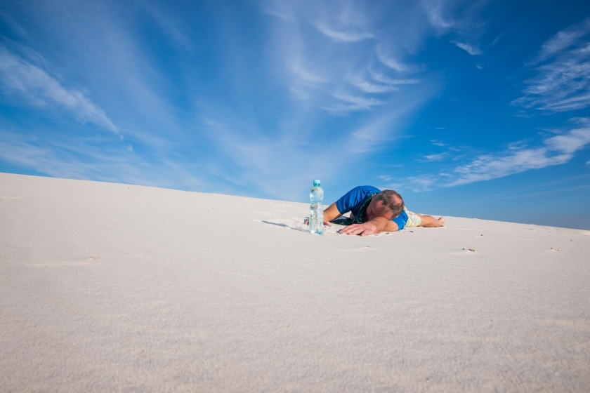 Tired man lies in the sand next to a bottle of water